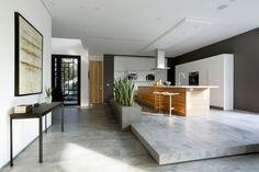 graue Bodenfliesen und Pflanzer mit Bogenhanf als Raumteiler