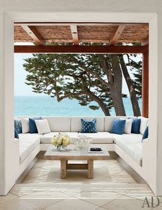 A terrace with views of the Pacific Ocean features a low oak table and patterned pillows made from antique textiles   archdigest.com