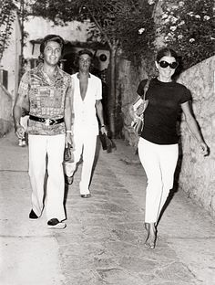 Jackie's outfit in this photo still works today—white cropped pants, black T-shirt, oversized sunglasses, hoop earrings, Hermès Trim bag (in Barenia and Toile) and her (possibly) Canfora sandals in her hand.