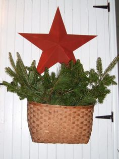 A small barn star and flat-backed basket filled with fresh-cut evergreens add a primitive touch to this front door. Created by HGTV fan Trudi Burns.