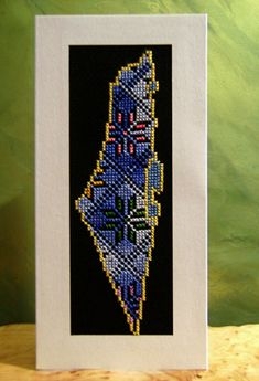 """Historic Map of Palestine    The outline of the map has been cross stitch embroidered in very fine stitches with DMC Pearl Cotton (yellow, blue, light-dark blue, green, peach pink, violet). It has been glued in a triple card so it can be used as a greeting card.    (21.10x10.30 cm; 8.31x4.06 """")"""