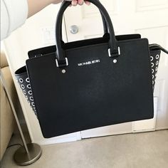 ⚜Michael Kors⚜Selma Large Satchel Absolutely stunning Grommet Selma purse in the color Black. size Large which is discontinued and hard to find. Was used several times•In very good condition•No major signs of use.   •AUTHENTIC GUARANTEED•   Original: $398 Now: only $215  Color: Black Size: Large Dimensions: 13 x 9.5 x 6 Exterior: black color with silver hardware Interior: MK monogram print fabric. One zippered pocket, four open slip pockets, and a key chain fob  •Comes with an…