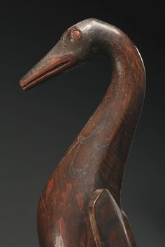 One of a  Pair of Haida Polychromed Wood Shaman's Rattles | in the form of a bird in flight, possibly a swan or oyster catcher, constructed of two hollowed sections joined together, with a long cylindrical handle, the upper section masterfully carved with outstretched wings, painted in black and red pigments with crest designs | Sotheby's