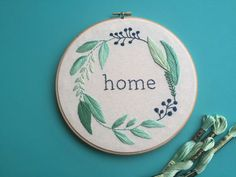 Home  A home is made even more sweet with this lovely embroidery hoop in shades of jade and blue. Delicate stitching of leaves and berries bring this