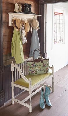 Vintage style: Use a flea market bench to designate mudroom space in an entry hallway. This vintage find nestles snugly under coat hooks to create a place for the family to put on shoes and hang hats.