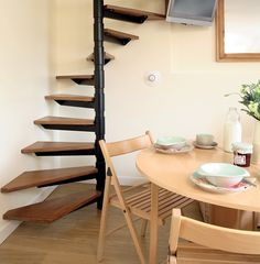 3 Small Space Solutions in 1 Tiny Kitchen Corner: lower stairs are to the back so area in front of stairs is usable; folding chairs can be out of the way when not in use; and TV is mounted high. Small Space Stairs, Small Space Kitchen, Kitchen Corner, Small Spaces, Stairs Kitchen, Kitchen Shelves, Small Apartments, Loft Staircase, Staircase Design