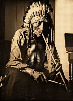 "Flat Iron, a medicine man of the Oglala Sioux, was raised by Sitting Bull. He had nine wives, 75 children and lived to be 107 years old. He gave Joseph Henry Sharp a prime tanned elkskin and said it was the ""best you can find in two days ride in any direction."""