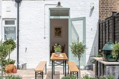 The outdoor space features a German Biergarten Table and hand-built BBQ with a Big Green Egg. The back facade is painted Dulux Pure Brilliant White and the door is Farrow & Ball Green Blue. Rustic Outdoor, Outdoor Dining, Outdoor Spaces, Outdoor Decor, Outdoor Ideas, Fresco, Balkon Design, London House, Green Eggs