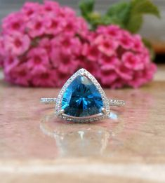 This is a custom order to make you a brilliant ring with a large 7.29 carat trillion cut London Blue Topaz set among .54 carats of natural pave set diamonds in a trillion halo setting made of 14kt white gold. See the photo of the topaz, this is the actual stone you will receive with your order. This would make any bride-to-be happy to show off this amazing ring. Just include your ring size, and color of gold (rose, white, or yellow) in the notes to seller upon checkout. All ring sizes over 8…