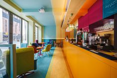 playfully contrasting fluoro elements against more subtle shades, the interior of this cafe in poland stands out as an easy-to-spot location.