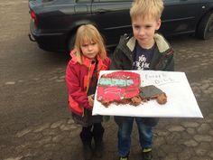 Børnebørn med en kage lavet som deres fars lastbil der nu skulle på pension.