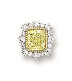 FANCY YELLOW DIAMOND AND DIAMOND RING. Centring on a cut-cornered rectangular…