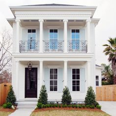 New Orleans Millworks Traditional Exterior and Balcony Black Door Dentil Trim Filagree Balcony Railing Ionic Columns Pale Blue Shutters Porch Columns Porch Light Sash Door Topiary Two Story White House White Siding | Finefurnished.com