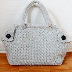 Derek is a crochet bag made with simple dc and sc stitches. It has a classical shape of a satchel and crochet handles to match. The opening is supported by wooden rods for a firm shape, and folded corners and buttons give the bag it's character. A printed cotton lining is the extra detail to finish off.