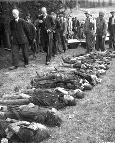 Sudeten German civilians are forced to walk past bodies of 30 Jewish women starved to death by SS troops in a 300 mile march across Czechoslovakia. Buried in shallow graves in Volary, Czechoslovakia, the bodies were exhumed by German civilians working under direction of Medics of 5th Infantry Division, U.S. Third Army. Coffins are awaiting the remains, which were eventually buried in the Volary cemetery.