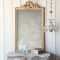 Eloquence, Inc.Antique Mirror Opulent Louis XVI style antique mirror in a gold gilt finish. The crest is detailed with a radiant laurel leaf, quiver, and torch motif