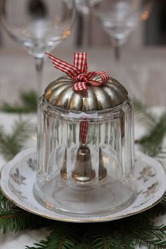 Drill a hole in the bottom of a vintage cup or glass. Then string a ribbon with a small bell attached through the hole.