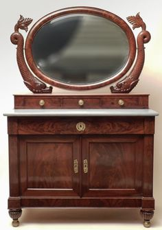 Mahogany Empire Ormolu Mounted Marble Top Mirrored Cabinet, circa 1820 - 40 oval mirror with carved dolphin supports above three drawers on a marble top base with a long drawer above two doors on melon reeded feet with brass balls