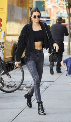 Get some style inspirations from Kendall Jenner's best outfits. Black cowboy jacket with tassels, a crop top, acid wash jeans and black boots.