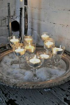 using tea llights in wine glasses and it appears they have used some kind of salt to look like sand or snow...