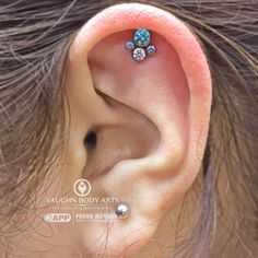 Our client Maria was an absolute pleasure to work with. After much consideration she decided on this anatometal​ cluster with mint green, arctic blue and CZ gems set in titanium that we anodized purple. We love the way this looks in her fresh helix piercing. Thanks so much, Maria!vaughnbodyartsMonterey, CA