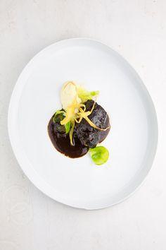 Langsam in Rotwein und Rinderfond geschmorte Schweinebäckchen mit Pastinaken-Püree und gezupften, in Butter gebratenen Rosenkohl-Blättern.