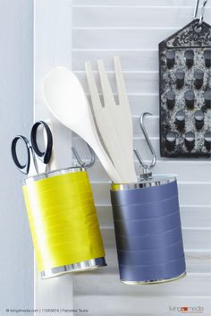 Decorated tin cans being used as storage tins for kitchen utensils hanging on a wall | © living4media | Franziska Taube | 11053874