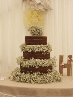 A large three tier naked chocolate wedding cake with fresh gypsophila flowers.