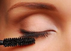 Woman applying black mascara on the eyelashes. Close-up image.