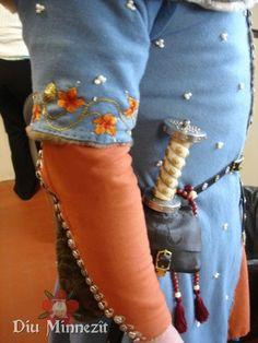 Detailaufnahme der Stickereien am Surcot, der Perlen und des Dolches mit Tasche und Gürtel