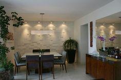 Revestimento em alto relevo e iluminação proporcionam um interessante efeito de luz e sombras. Cajuí Design de Interiores