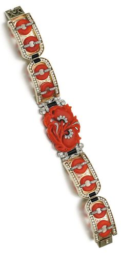 An Art Deco coral, onyx, seed pearl and diamond bracelet, 1920s. The central plaque set with carved coral in the shape of pomegranates with rose and single-cut diamonds, between openwork plaques set with coral hololiths, onyx and seed pearls, indistinctly numbered, French assay marks.