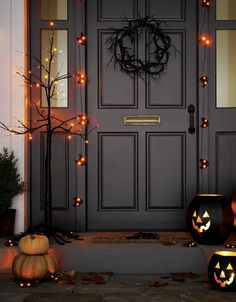 Orange LED lights add spooky illumination to bare-branched, black Halloween tree decoration that can be set up indoors or out.