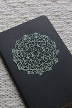 Sacred Geometry - the physical manifestation of the invisible threads that connect all things. This 3.5 x 5.5/9x14 cm genuine Moleskine cahier notebook is thoughtfully and meditatively embellished by hand one stitch at a time to create the mandala motif seen on the cover. Black