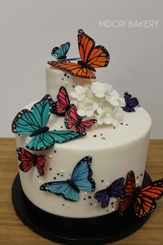 Hand cut and painted sugar butterflies and flowers on 2-tier cake by Midori Bakery