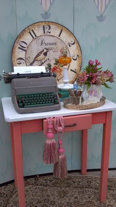 Shabby chic table scape with vintage typewriter, hobnail lamp, books, biscuit jar, clock face and flowers | celery city trading company for Vintage Events & Rentals
