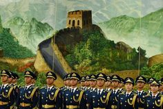Chinese soldiers in front of a painting of the Great Wall of China in Beijing's...