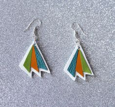 White leather earrings with orange, green and turquoise decoration. The lenght of them is approximately 3.5 cms. Colors might appear slightly different on the screen than in real life. My creations come from a smoke and pet free environment.