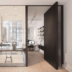Uniform Wares offices include a glazed watch-testing room and a pivoting timber door