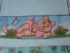 Detalhe de pintura a mão na fralda de boca, pintada em toda a faixa especial para pintura, com motivo ursinha no jardim.