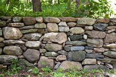 Build a beautiful border with a fence that uses stone solo or mixed with other materials.