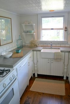 Framed map, farmhouse sink, white appliances, beadboard, sisal rug