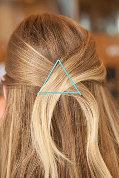 Pull small sections of hair from each side of your head and cross them in the back. While holding your hair in place, take a bobby pin and slide it in horizontally over the crossed section. Then take another bobby pin and slide it upward at a diagonal angle to set the right side. Repeat this on the left to complete the triangle.