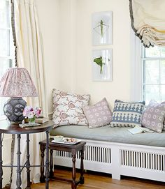 In the living room, John Robshaw throw pillows help cushion a radiator-obscuring bench. The insect photos, by Linda B. Horn, hang on a wall painted White Dove by Benjamin Moore.   - CountryLiving.com