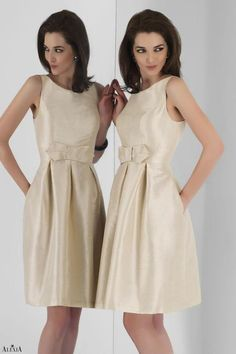 Champagne poly shantung cocktail length dress featuring a pleated skirt with empire waistband and bow.