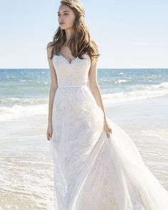 A-line wedding dress in ivory lace with 'V' neckline and spaghetti straps. Features sheer lace details at back, narrow ribbon at waist natural waist, and lace and tulle skirt with raw hem and chapel train.