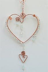 """Heart Wire Suncatcher created by: Coirnini Company © ™ Custom Made For You:  This Custom Request by request from one of our fans on our page. The Bliss Heart is adorn by aqua glass beads and a clear crystals with a Heart Shaped Charm If you would like to """"Purchase a Bliss Heart like this one, email us at coirnini@gmail.com """" Display in a Window, Rearview Mirror or a place you love. www.facebook.com/coirninico or http://www.coirnini.com"""