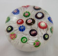 "Antique glass Clichy paperweight with scattered millefiori canes on an upset muslin ground, ca. 1850. This mini paperweight features one pink and green rose cane, called a ""cabbage rose"" cane, near the edge of the design. $1,650.00"