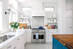 An Entertainer's Space: After - Before-and-After Kitchen Makeovers - Southernliving. A new island doubles as a buffet, and the statement paint coat on the base cabinets and walnut top make it the focal point of the room. Inspired by history, NeJame selected handmade glazed subway tile, marble countertops, and more traditional cabinet doors—Shaker style with bead detailing.