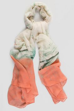 The oblong shape Miami Scarf features an abstract print of the vibrant scene of the infamous city. The melding ivory, green & coral colors allude to a shoreline at sunset. Pair with a casual outfit for a hip look.